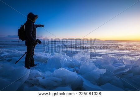 Photographer take pictures on the frozen river during sunset. A man points a finger at dawn