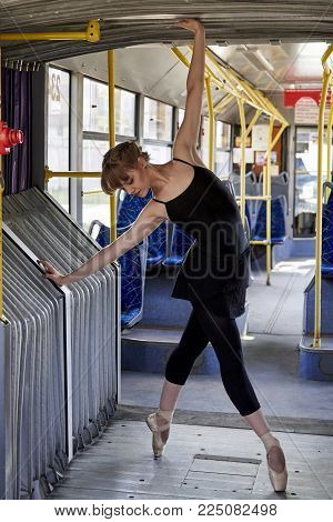 A ballerina dances in town transport near the handrail