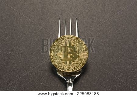 Golden Bitcoin physical coin on a fork illustrating a cryptocurrency split concept.