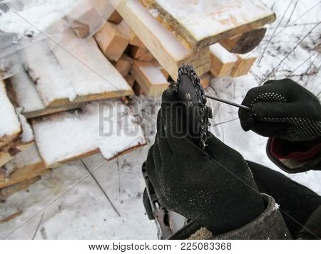 Manual sharpening chainsaw chains close-up - illustrative photo. Male hands in black gloves hold the sharpener and blade of the saw against a background of white snow in winter
