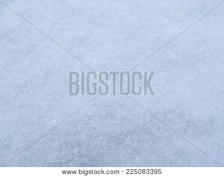 Beautiful gentle texture of young fluffy snow in winter. The light blue smooth surface is covered with a layer of delicate snowflakes