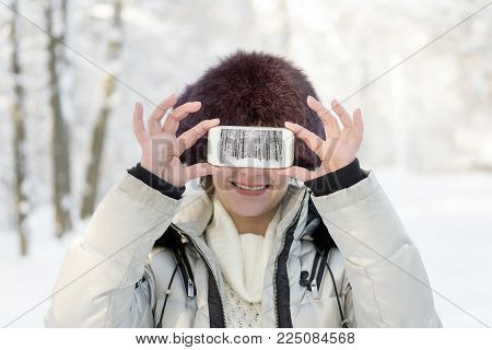The girl in the fur hat is holding the phone at eye level. On the screen, the landscape is telephoned. Winter, day.