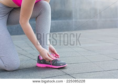 Woman tying shoes laces before running, getting ready for jogging in park, closeup, copy space, crop