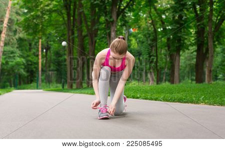 Woman tying shoes laces before running, getting ready for jogging in park, copy space