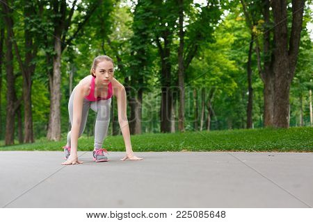 Ready, steady, go. Young sporty woman in starting position at city park, ging to begin her cardio training. Health and fitness concept