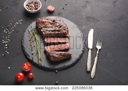 Cut rare rib eye steak with herbs and spices on dark background, served with tomato, restaurant serving with cutlery, top view