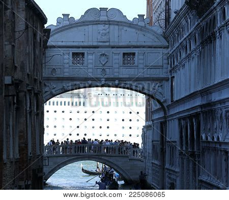 Venezia, Italy - July 14, 2015: Bridge of Sighs with many people and the huge cruise ship in the background on the Giudecca Canal