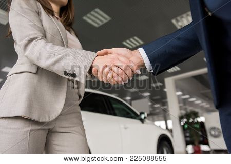 Low angle close up of car salesman shaking hands with woman buying new car in dealership showroom