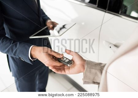 High angle close up of car salesman giving keys to client standing next to white luxury car, copy space