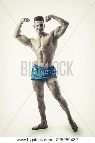 Good Looking Young Gym Fit Man Showing His Sexy Six Pack Abs While Looking at the Camera. on Light Background.