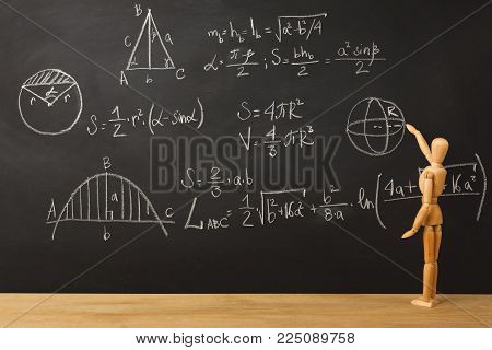 Educational background. Wooden marionette writing mathematics sums with chalk on blackboard. Back to school concept