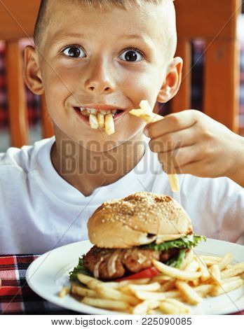 little cute boy 6 years old with hamburger and french fries making crazy faces in restaurant close up