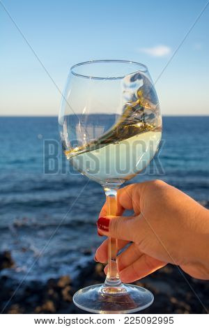 Tasting Of Glass Of Cold White Wine On Outdoor Terrace With Sea View
