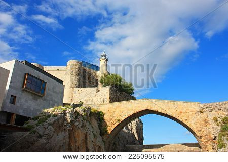 White lighthouse under the blue cloudy sky in Spain