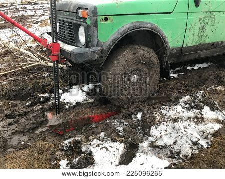 A wheel car lift rack Jack. Wheel green machine raised out of the mud by means of a rack Jack. The wheel is covered with a thick layer of dirt. Around the mud and snow.