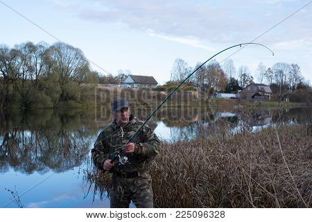 A man catches fish in the lake. Around the autumn - dry grass, trees with fallen leaves. The lake reflects the sky with clouds and trees around the lake and village on the shore of the lake.