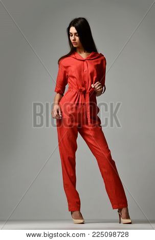 Young beautiful woman posing in new casual red fashion costume dress with pants and hood full body on grey background