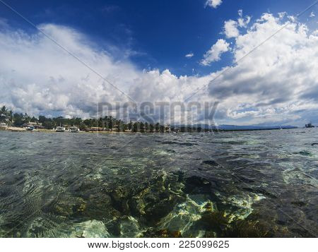 Sea and sky double landscape. Tropical seascape split photo. Double seaview. Underwater coral reef. Above and below waterline border. Exotic seashore. Coral reef and green coast. Shallow seawater