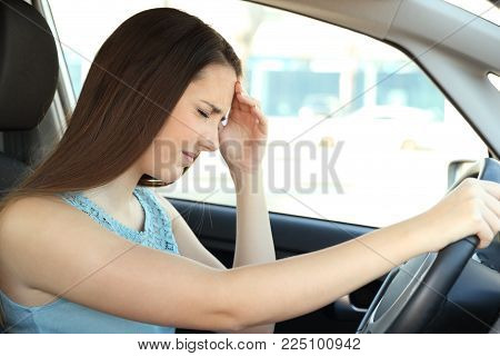Side view portrait of a driver suffering migraine driving a car