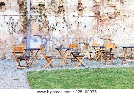 Courtyard outdoor cafe area with wooden tables and chair, green grass lawn and ruined shbby brick wall on the background. Open air space. Fusion of style.
