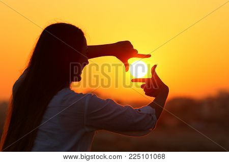 Backlight portrait of a woman silhouette framing sun with fingers at sunset