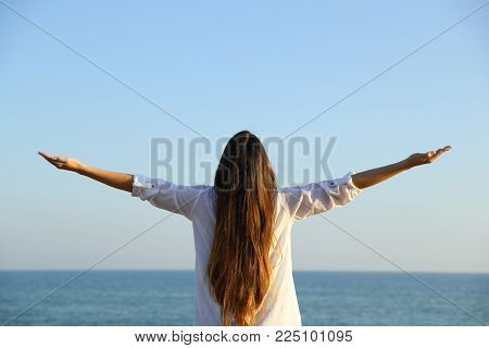 Back view portrait of a woman outstretching arms outdoors to the sea and sky