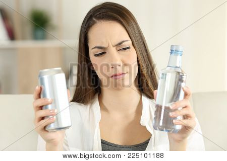 Front view portrait of a pensive woman doubting between soda drink and water at home