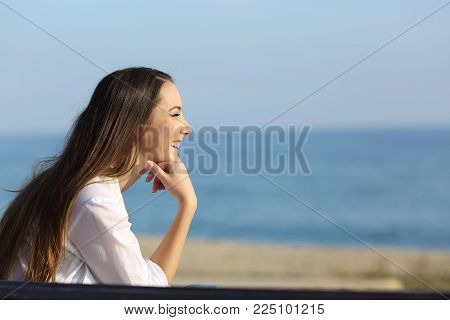 Side view portrait of a smiley woman looking forward on the beach in a sunny day