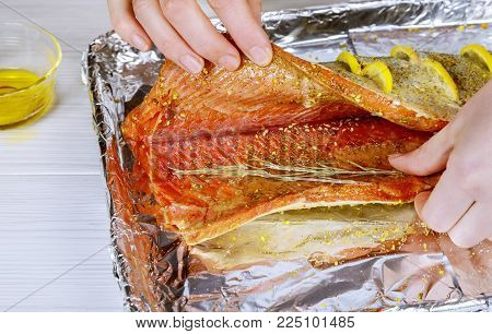 Marinated salmon with different spices Freshly marinated salmon fillet on metallic plate cutting board