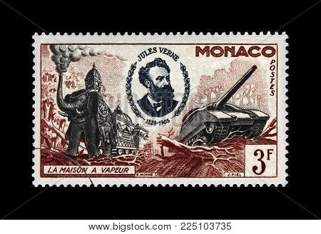 MONACO - CIRCA 1955: canceled postal stamp printed in Monaco shows Jules Verne (1828-1905), famous science writer and steam house, military machines, circa 1955. Vintage stamp isolated on black background.