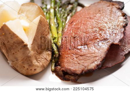 organic prime rib roast dinner with baked potato and asparagus