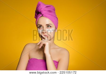 woman with a towel on her head apply patches under the eyes