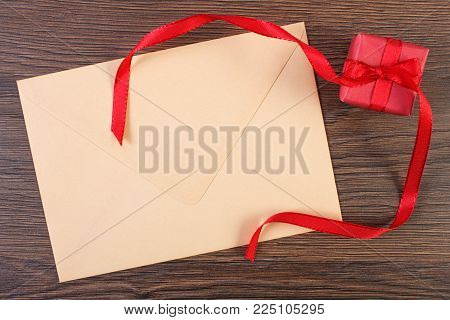 Wrapped gift with ribbon and love letter in envelope, decoration for Valentines Day, copy space for text