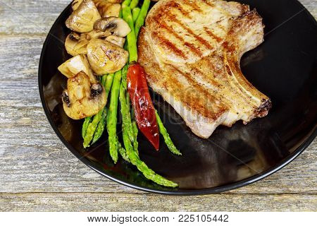 Grilled steak with Grilled striploin sliced steak. Juicy thick grilled steak seasoned fresh a black plate with salt and pepper