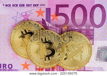 Golden Bitcoins with five hundred Euro Banknotes as background