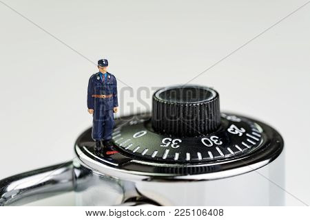 Security, safety or secret awareness concept, with miniature figure security guard standing on circle combination lock pad with turning code.