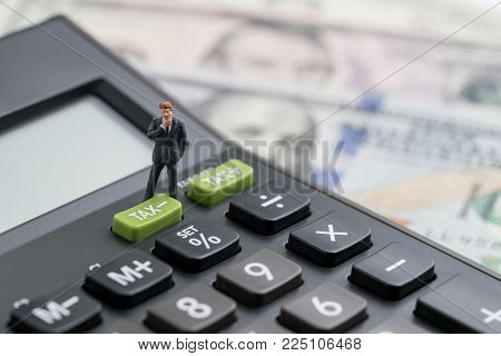 Miniature people business man thinking and standing with TAX minus button on calculator with background of blurred US Dollar banknotes, United States government tax overhaul, cuts or reduce concept.