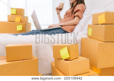 Freelancer woman working sme business at office in home interior smile checking order from labtop computer for customer and online delivery box for ready packing in bedroom and drinking coffee relax