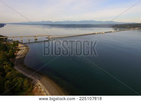A Boat Moves Along Heading South Going Under The Hood Canal Bridge Near The Olympic Mountain Range I