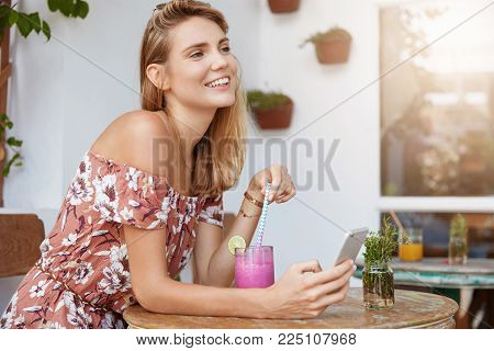 Indoor Shot Of Pleasant Looking Female Dressed In Summer Blouse, Enjoys Tasty Smoothie While Message