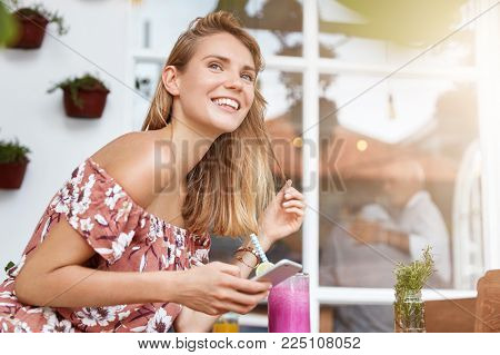 Happy Young Woman In Summer Clothing Chats With Friends Via Social Networks, Uses Modern Cellular, G