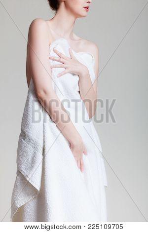 Beauty of female body. Naked woman covering herself with white bath towel. Attractive lady in spa massage. Harmony and vitality.
