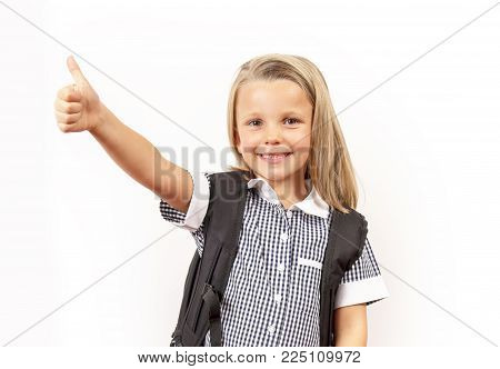 young beautiful and happy child girl 6 to 8 years old blond hair and blue eyes smiling excited wearing school uniform and backpack isolated on white background in kid education concept
