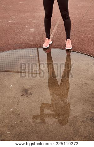 one person exercise, sport clothes, tights, puddle reflection in water