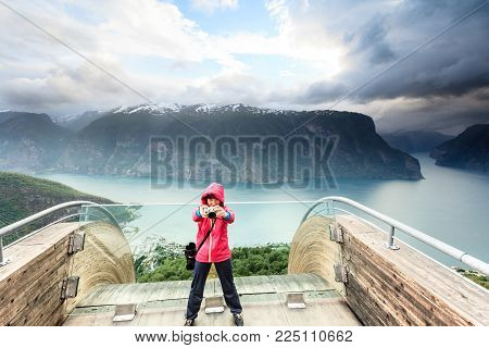 Tourism and travel. Woman tourist nature photographer taking photo with camera, enjoying Aurland fjord landscape from Stegastein lookout, Norway Scandinavia.