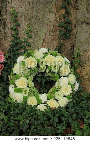 white sympathy wreath or funeral flowers near a tree, white roses and mums