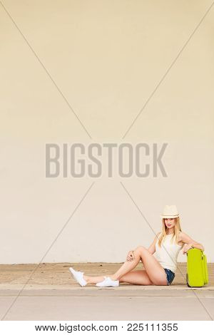 Travel, adventure, teenage journey concept. Woman wearing denim shorts, white top and sun hat suitcase holding suitcase on wheels hitchhiking, sitting and relaxing during trip