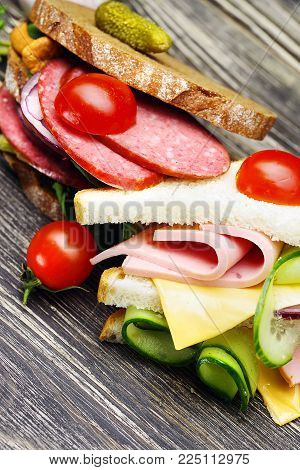 Close-up of fresh appetizing sandwiches with salami, vegetables, ham and cheese on a wooden table.