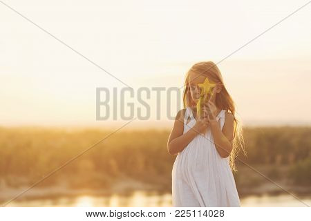 A nice little girl hides her face behind a toy on the river bank at sunset.