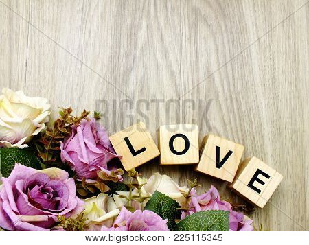 Love Word Wooden Block With Artificial Roses Flowers Decor And Space Background